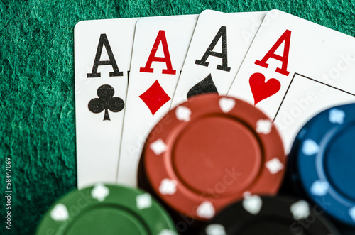 four aces with casino chips on green table