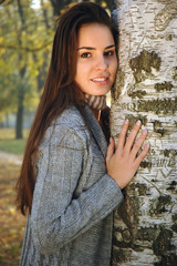 Young woman leaned on a birch