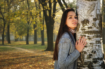 young pensive woman leaned on birch in autumn park