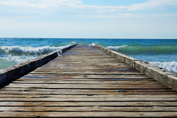 Wooden pier leading into the blue sea