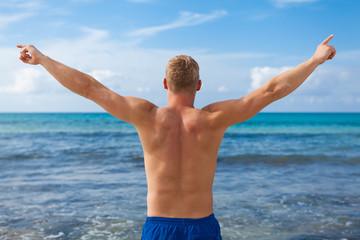 sportlicher junger mann in badehose am strand im urlaub