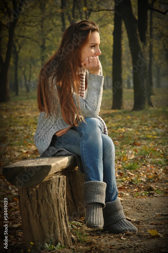 Pensive woman sitting on bench in autumn park