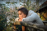beautiful woman leaning chin on old wooden fence, thinking