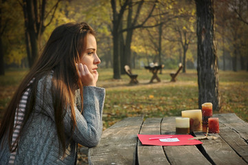 woman at table in autumn park with paper and candles