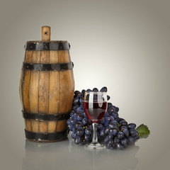 barrel, bottles and glass of wine and ripe grapes