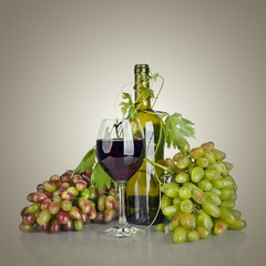 bottle, glass of wine and ripe grapes
