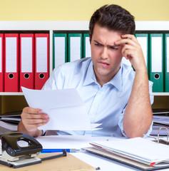 Mann am Schreibtisch hat Sorgen