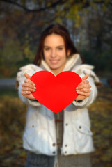 woman out of focus holding paper heart