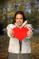 beautiful woman in white jacket holding paper heart