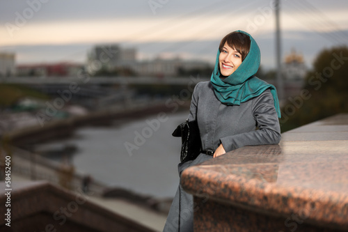 Happy young woman in classic coat on the urban background