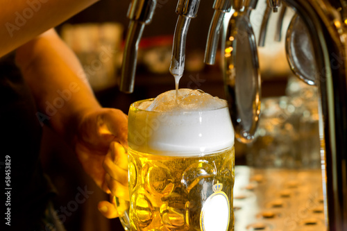 Man pouring a tankard of frothy beer