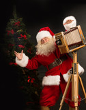 Santa Claus taking picture with old wooden camera standing near