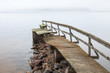 Old ruined wooden pier on the lake in foggy morning
