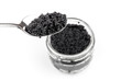 Black caviar in full glass jar and teaspoon isolated on white ba