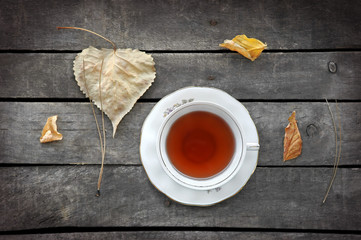 autumn tea in white vintage cup on old wooden table