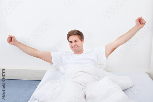 Young Man Stretching In Bed