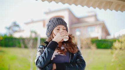 Young, attractive woman drinking coffee outside