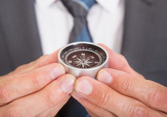 Businessman Holding Compass