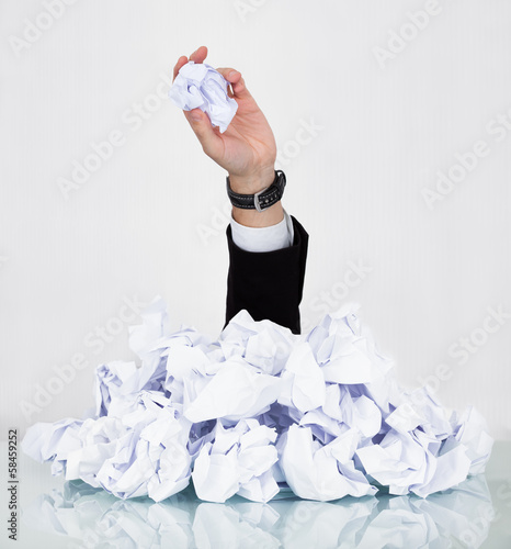 Person Under Pile Of Crumpled Paper