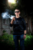 Portrait of young man in sunglasses smoking marijuana joint