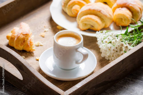 Breakfast in bed with espresso, flower and croissant