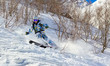 Skier on a steep slope in the forest zone