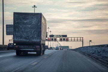 Truck on dirty winter ring road in the evening.