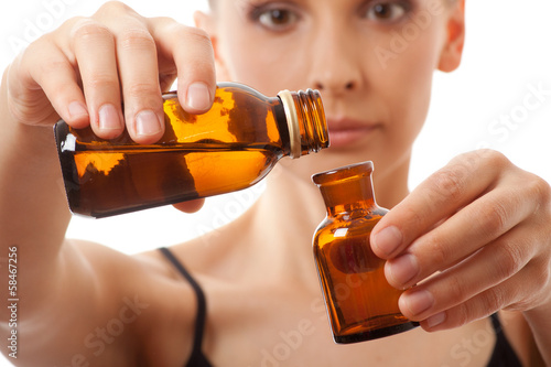 Young woman holding two bottles of medicine