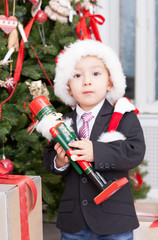boy stands near Christmas fir-tree with nutcracker in hands