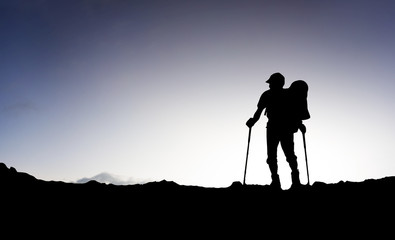Silhouette of a tourist on the mountain top.