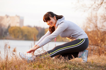 Happy middle-aged woman doing  stretching exercises