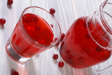 cranberry juice with berries in a glass on the table