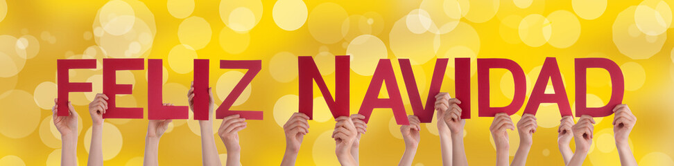 People Holding Feliz Navidad with Golden Background
