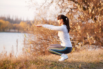 Young woman doing exercises at sunset