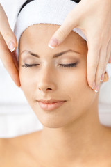 Headshot of naked woman with closed eyes getting face massage