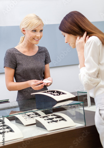 Shop assistant helps lady to choose jewelry at jeweler's shop