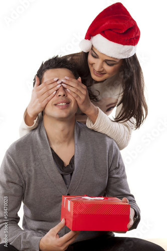 Wife surprising her husband with a christmas gift