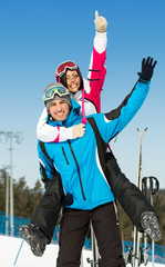 Half-length portrait of happy couple of downhill skiers have fun