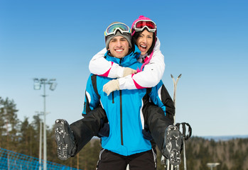 Half-length portrait of happy couple of skiers have fun
