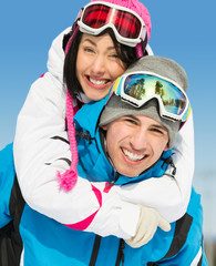Portrait of happy couple of downhill skiers have fun