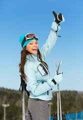 Half-length portrait of female skier thumbing up