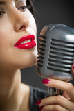 Headshot of female singer keeping microphone on grey background