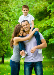 Happy family of three. Father keeps son on shoulders