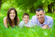 Happy family of three lying on grass
