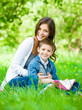 Mom and son with book sitting on green grass in park