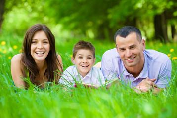Happy family of three lying on grass