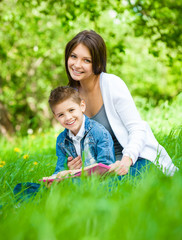 Mother and son with book sitting on green grass