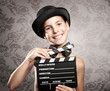 happy little girl holding a movie clapper
