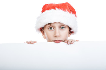 Cute funny child Santa looking from behind big white board
