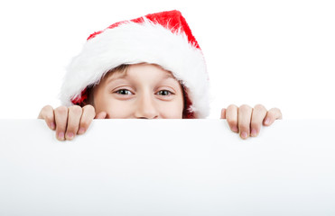 Beautiful shy child Santa standing behind a white board